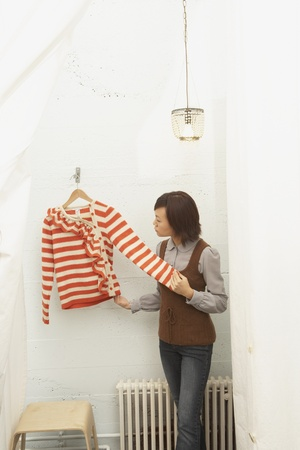 Young woman trying on a sweater in fitting rooms Stock Photo - 16070285