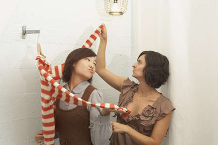 shopping buddies: Young woman trying on a sweater in fitting rooms