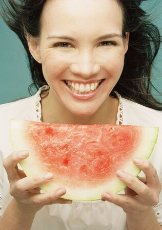 Young woman eating a seedless watermelon Stock Photo - 16070276