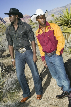 tipping: Young men in cowboy outfits posing for the camera