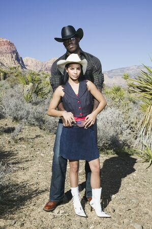 wooing: Young couple in cowboy outfits posing for the camera