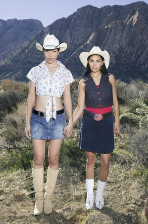 Lesbian couple in cowboy outfits posing for the camera Banco de Imagens