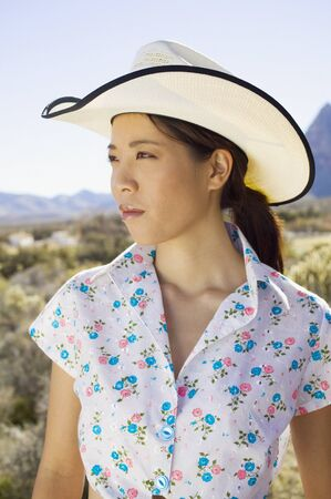spectating: Young woman in cowboy hat posing for the camera