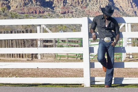 leaning by barrier: Young man in cowboy outfit posing for the camera