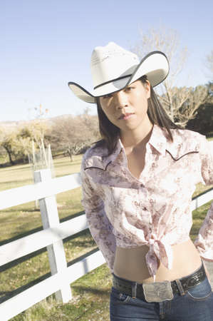 leaning by barrier: Young woman wearing a cowboy hat