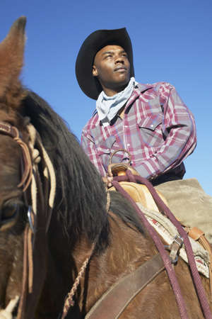 cowboy up: Young man in a cowboy outfit riding a horse