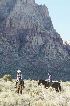 longshot: Young couple in cowboy outfits riding a horse LANG_EVOIMAGES