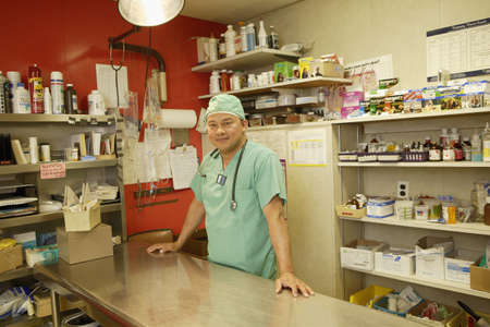office furniture: Pharmacist smiling for the camera behind counter