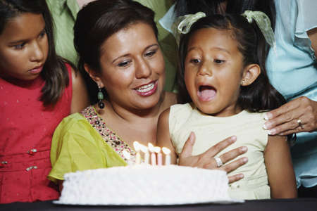 birthday party kids: Young girl blowing out the candles on her birthday cake