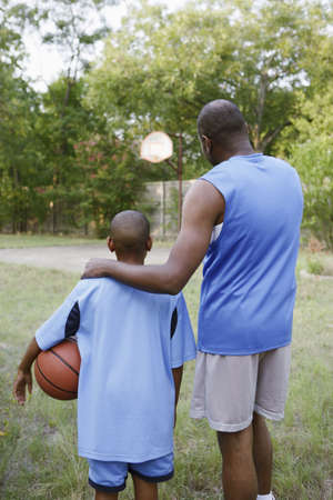 african descent ethnicity: Father and son looking at basketball court