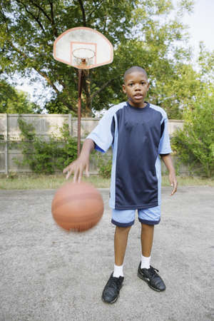 young fellow: Young boy dribbling basketball LANG_EVOIMAGES