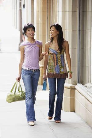 sidewalk talk: Two women walking on sidewalk