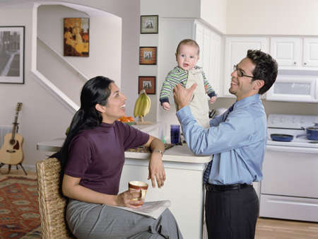 domestic: Couple playing with their baby in the kitchen