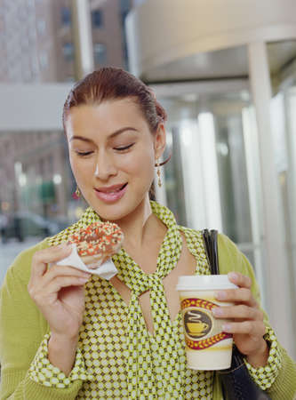 swindling: Businesswoman eating a donut LANG_EVOIMAGES