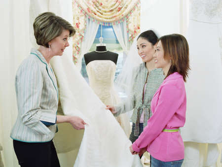 Tailor helping young women pick bridal fabric Stock Photo - 16089917