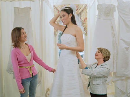 shopping buddies: Young bride-to-be trying on her gown