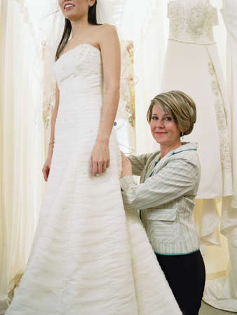 asian wedding: Young bride-to-be trying on her gown