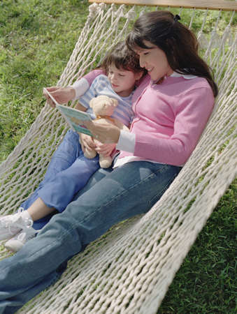 Mother and daughter reading in a hammock Stock Photo - 16089945