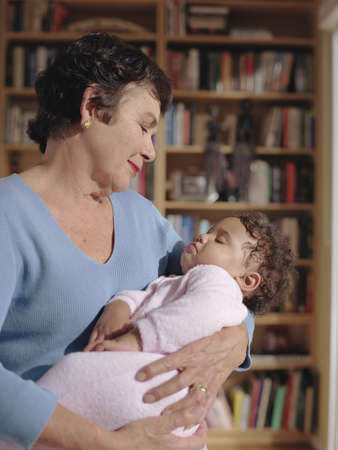 cradling: Middle-aged woman cradling her baby granddaughter LANG_EVOIMAGES