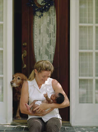 Woman holding a newborn baby on her doorstep LANG_EVOIMAGES