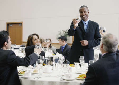 dining table and chairs: Businessman making a toast at lunch