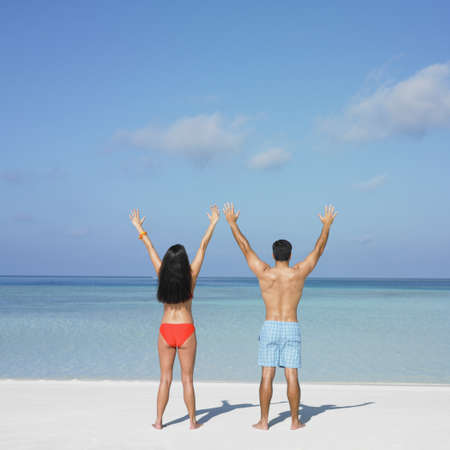 honeymooner: Couple standing on the beach LANG_EVOIMAGES