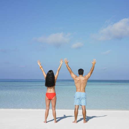 honeymooner: Pareja de pie en la playa LANG_EVOIMAGES