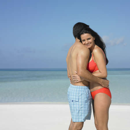 honeymooner: Couple hugging on the beach