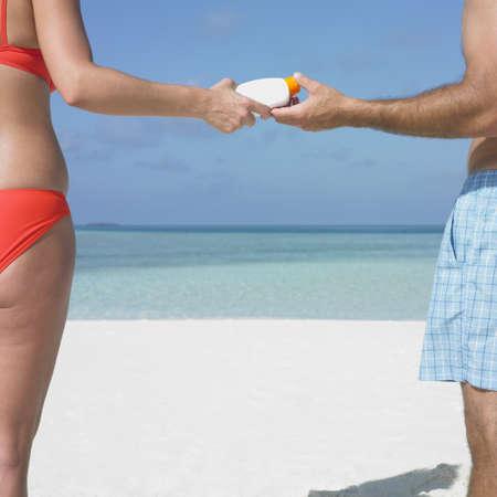 honeymooner: Pareja usar protector solar en la playa