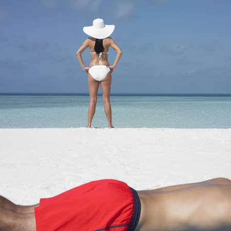 honeymooner: Mujer joven de pie en la playa, toma el sol novio