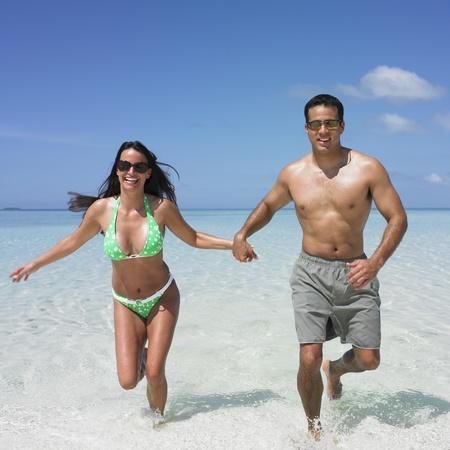 honeymooner: Pareja corriendo en la playa LANG_EVOIMAGES