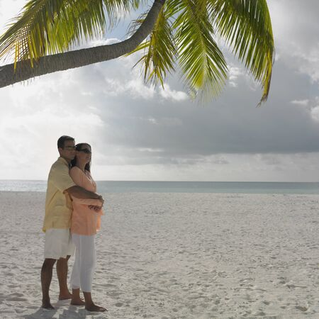 vacationing: Couple hugging on the beach