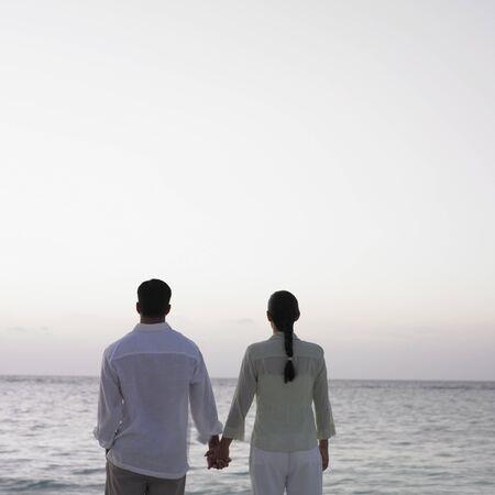 honeymooner: Couple holding hands at the beach
