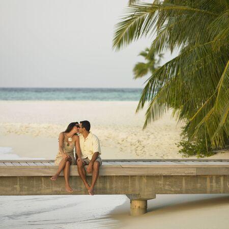 honeymooner: Couple kissing on a pier