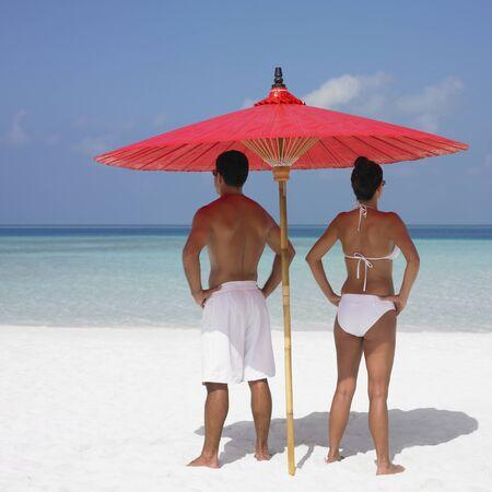 honeymooner: Pareja de pie bajo una sombrilla en la playa