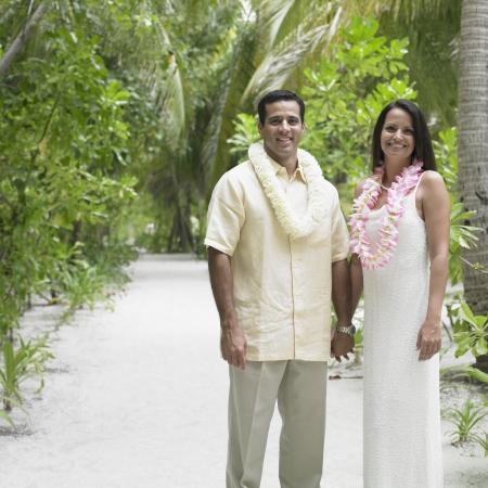 honeymooner: Couple holding hands outdoors LANG_EVOIMAGES