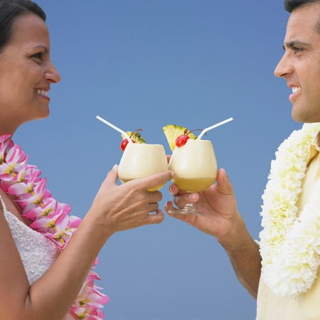 honeymooner: Couple toasting each other with tropical drinks