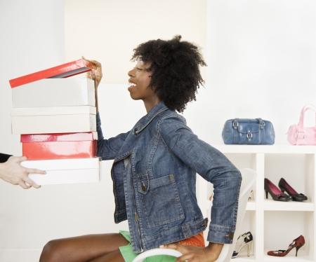 shoe boxes: Mujer joven que mira en cajas de zapatos LANG_EVOIMAGES