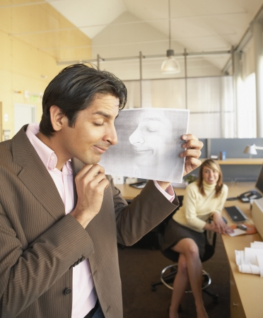 hilarity: Businessman examining print of womanís sleeping face