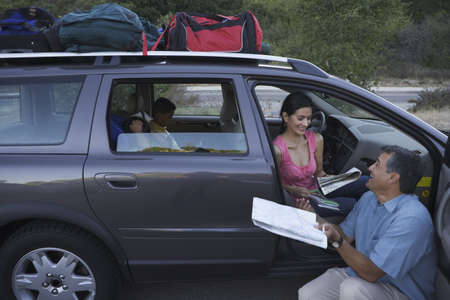 finding a mate: Man examining map by his family minivan