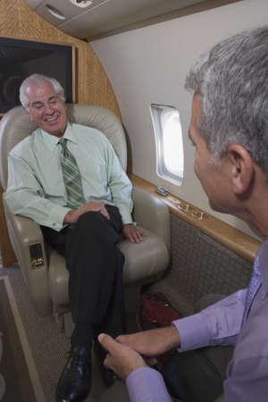 onboard: Businessmen talking onboard an airplane
