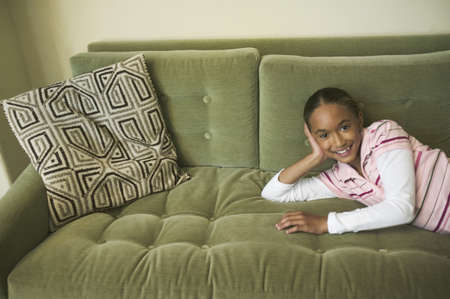 Young girl relaxing on a couch Stock Photo - 16090245
