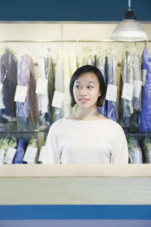 toiling: Asian drycleaner standing behind counter, Edmonds, Washington, United States