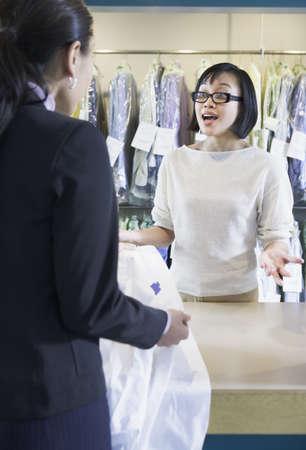 edmonds: Asian drycleaner talking to customer, Edmonds, Washington, United States LANG_EVOIMAGES