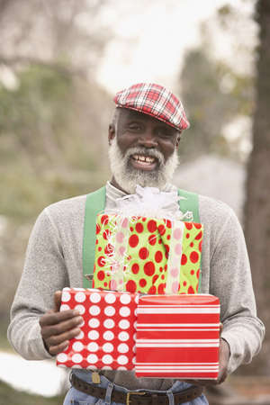 Senior African man holding presents, Richmond, Virginia, United States Stock Photo - 16090290
