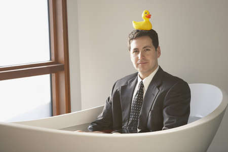 only mid adult men: Hispanic businessman sitting in a bathtub with a rubber ducky on his head, Richmond, Virginia, United States