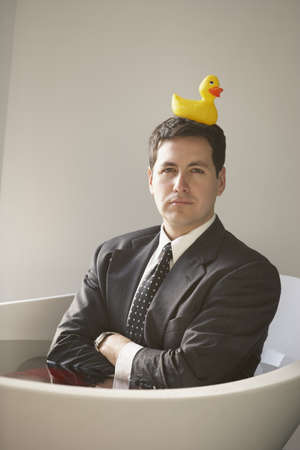 Hispanic businessman sitting in a bathtub with a rubber ducky on his head, Richmond, Virginia, United States Stock Photo - 16090308