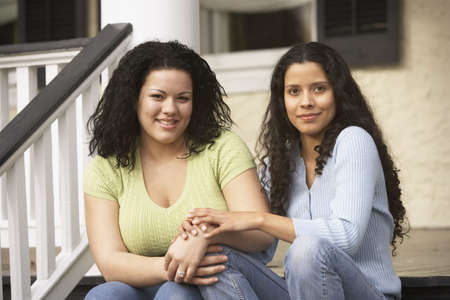 Hispanic sisters sitting on the porch holding hands, Richmond, Virginia, United States Stock Photo - 16090313