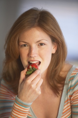 Young woman eating a strawberry, Richmond, Virginia, United States Stock Photo - 16090315