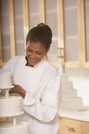 south american ethnicity: African female pastry chef next to a wedding cake, Richmond, Virginia, United States LANG_EVOIMAGES